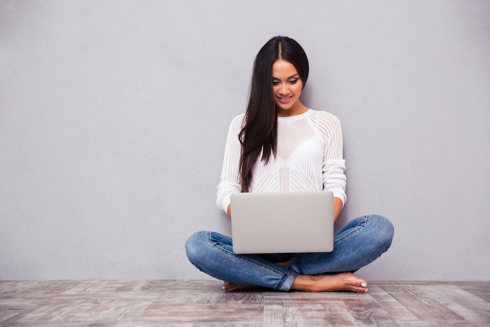 Portrait of a casual woman sitting on the floor with laptop